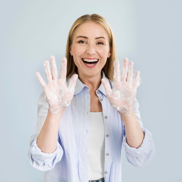Smileyvrouw die handen tonen die in zeep worden behandeld