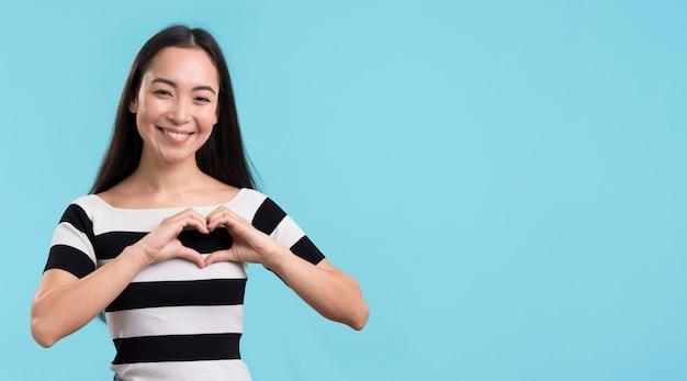 Smileyvrouw die hartvorm tonen