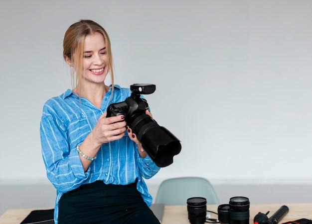 Smileyvrouw die in blauw overhemd de fotografiecamera bekijken