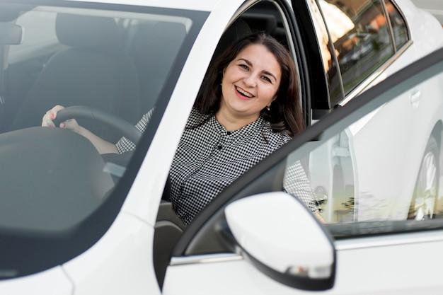 Smileyvrouw die in de bestuurdersstoel zit