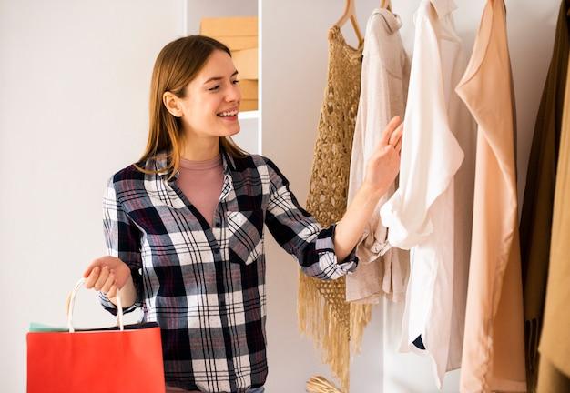 Smileyvrouw die in de garderobe kijkt