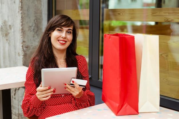 Smileyvrouw die items in de uitverkoop bestellen met behulp van tablet en creditcard