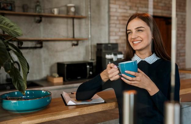 Smileyvrouw die koffie heeft tijdens een vergadering