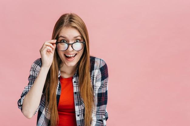 Smileyvrouw die met glazen de camera bekijken