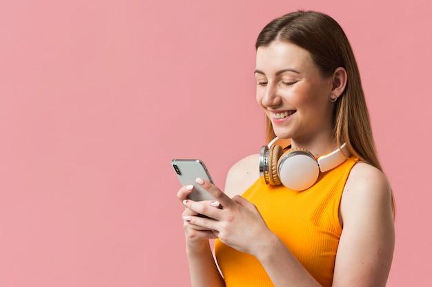Smileyvrouw die met hoofdtelefoons mobiel controleren