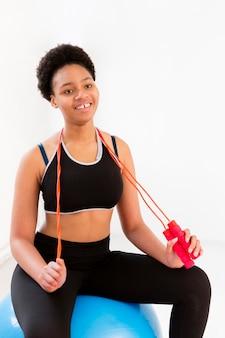 Smileyvrouw die met touwtjespringen uitoefenen