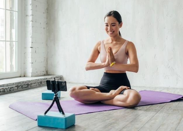 Smileyvrouw die op geschiktheidsmat mediteren