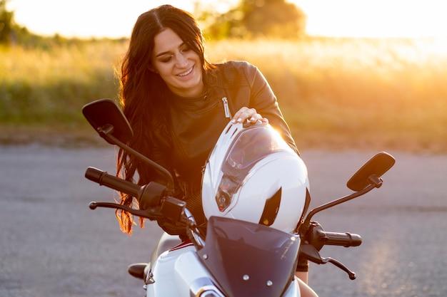Smileyvrouw die op haar motorfiets rust