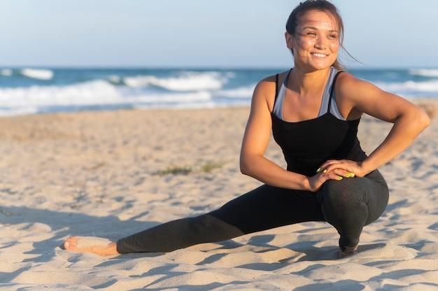 Smileyvrouw die op het strand uitwerkt
