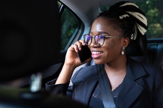 Smileyvrouw die op smartphone spreekt terwijl in haar auto