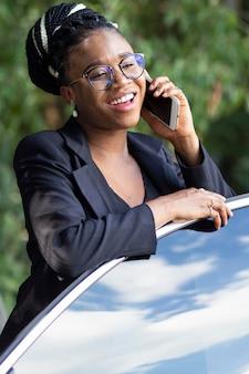 Smileyvrouw die op smartphone spreekt terwijl tegen haar autodeur leunt