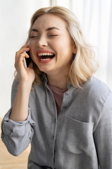 Smileyvrouw die op smartphone spreekt