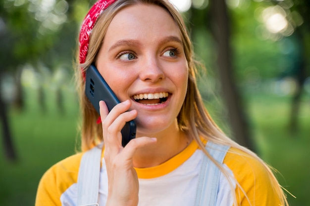 Smileyvrouw die op telefoon in openlucht spreken