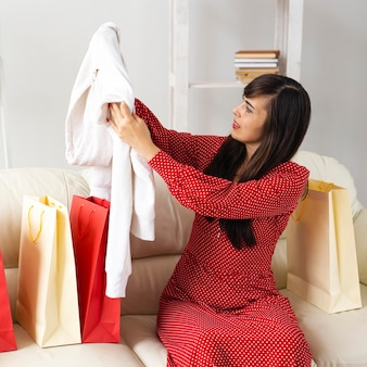 Smileyvrouw die punten controleert die zij tijdens het winkelen in de uitverkoop heeft ontvangen