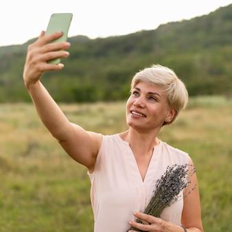Smileyvrouw die selfie in openlucht nemen