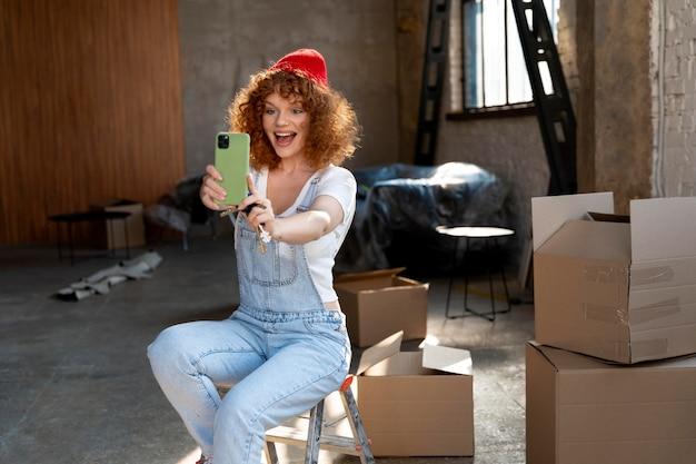 Smileyvrouw die selfie met smartphone neemt in haar nieuwe huis