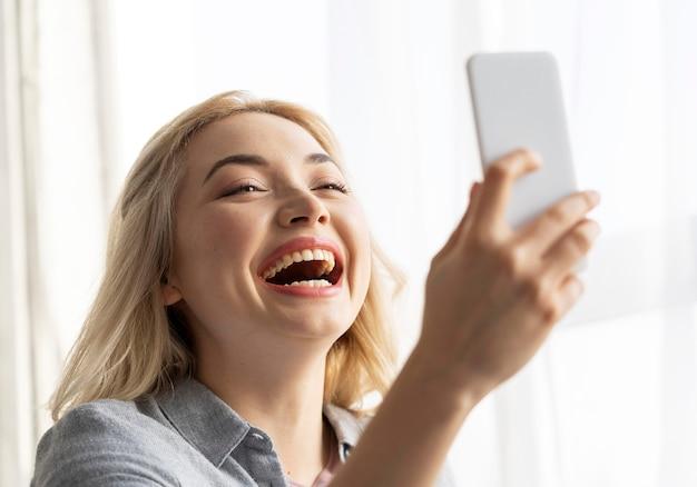 Smileyvrouw die selfie met smartphone neemt
