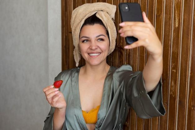 Smileyvrouw die selfie middelgroot schot neemt