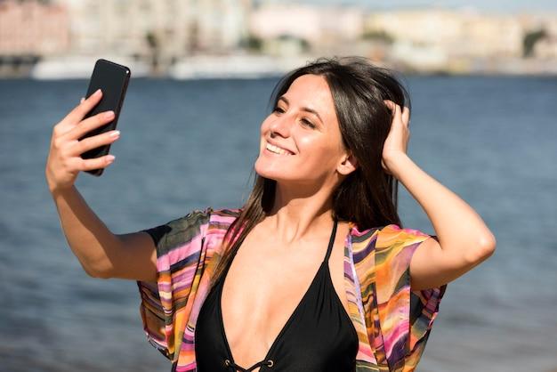 Smileyvrouw die selfie op het strand neemt