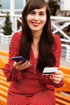 Smileyvrouw die smartphone en creditcard gebruikt om online verkoop te winkelen