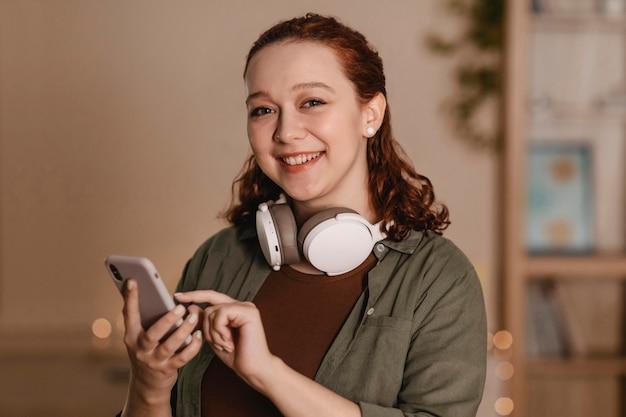 Smileyvrouw die smartphone en hoofdtelefoons gebruikt