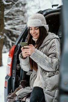 Smileyvrouw die smartphone uit de auto gebruikt tijdens een roadtrip