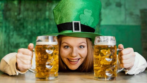 Smileyvrouw die st. patrick's day met een drankje aan de bar