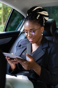 Smileyvrouw die tablet bekijkt terwijl op de achterbank van haar auto