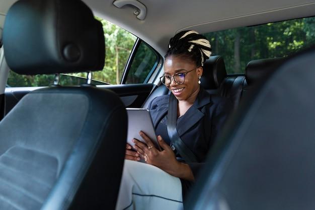Smileyvrouw die tablet bekijkt terwijl zij op de achterbank van haar auto zit