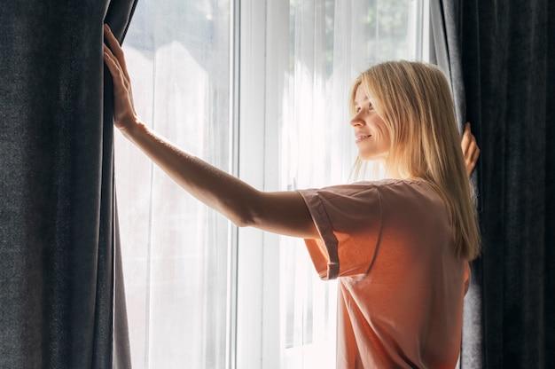 Smileyvrouw die thuis door het raam kijkt tijdens de pandemie