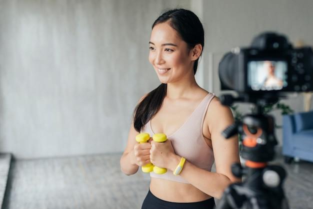 Smileyvrouw die thuis in sportkleding vlogt