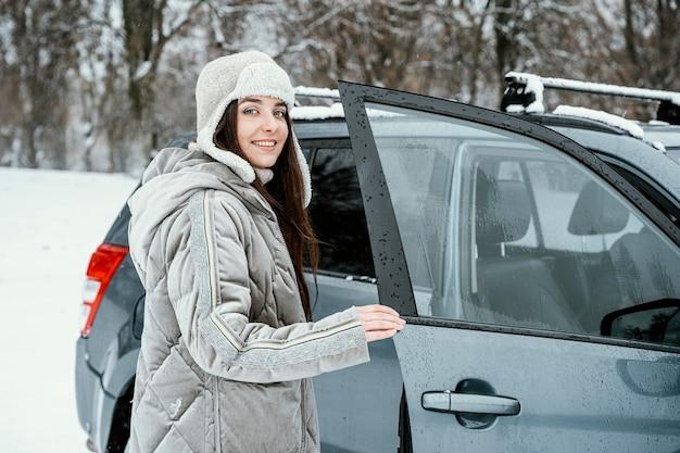 Smileyvrouw die tijdens een roadtrip weer in de auto komt