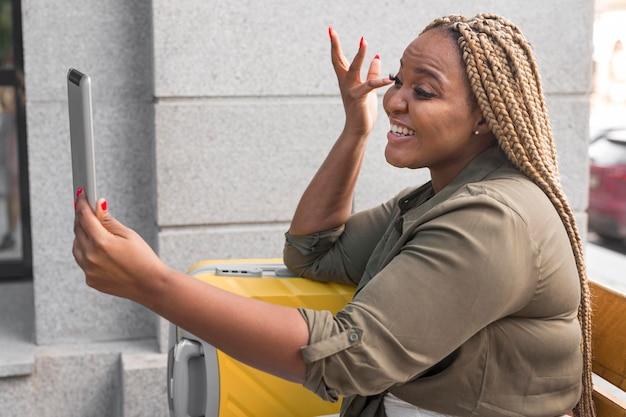 Smileyvrouw die tijdens het reizen een videogesprek op haar tablet heeft