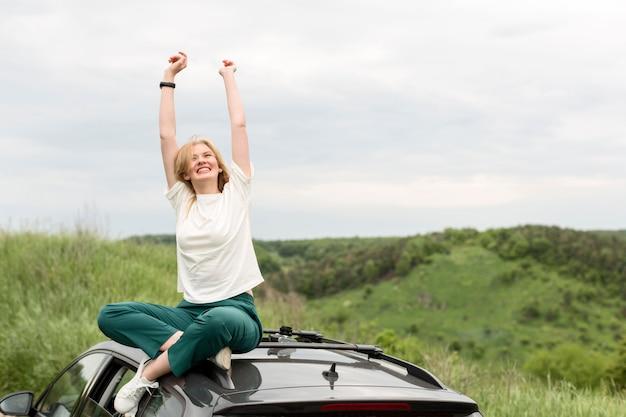 Smileyvrouw die van aard bovenop auto genieten