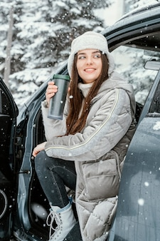 Smileyvrouw die van de sneeuw geniet terwijl op een roadtrip