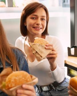 Smileyvrouw die van een hamburger geniet