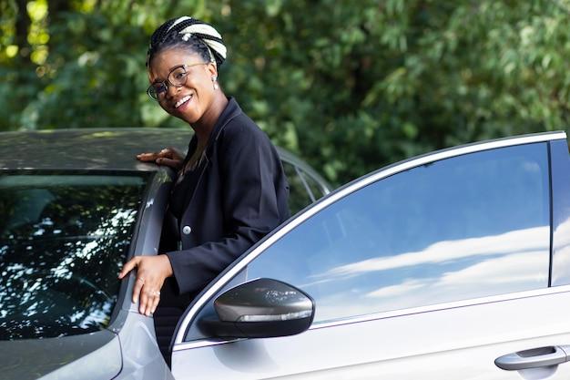 Smileyvrouw die van haar gloednieuwe auto houdt