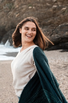 Smileyvrouw die van haar tijd geniet bij het strand