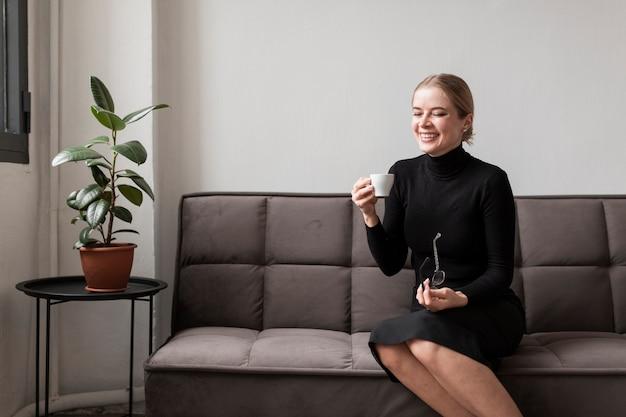Smileyvrouw die van kop van koffie genieten