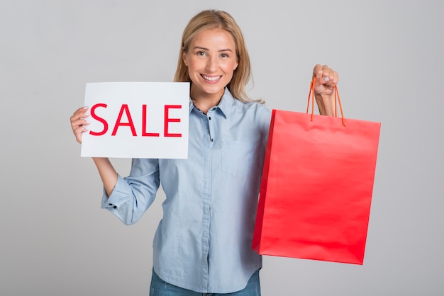 Smileyvrouw die verkoopteken en het winkelen zak steunt