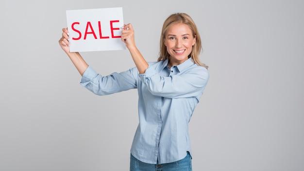 Smileyvrouw die verkoopteken steunt