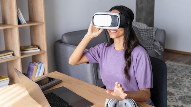 Smileyvrouw die virtuele werkelijkheidshoofdtelefoon thuis met laptop gebruikt
