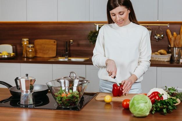 Smileyvrouw die voedsel in de keuken thuis voorbereidt