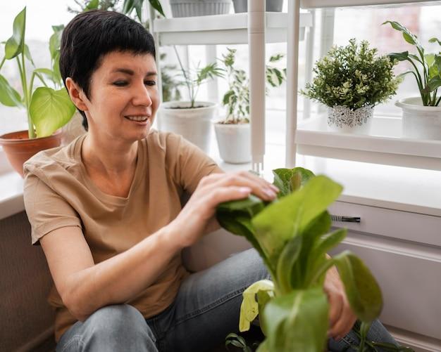 Smileyvrouw die voor kamerplanten zorgt