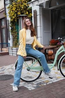 Smileyvrouw die zich voordeed op haar fiets in de stad