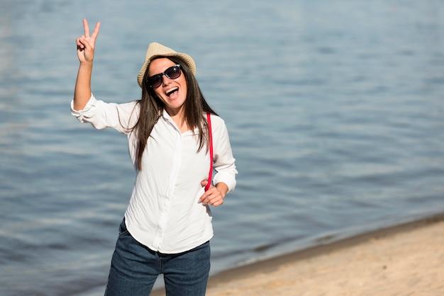 Smileyvrouw die zich voordeed op het strand en vredesteken maakt
