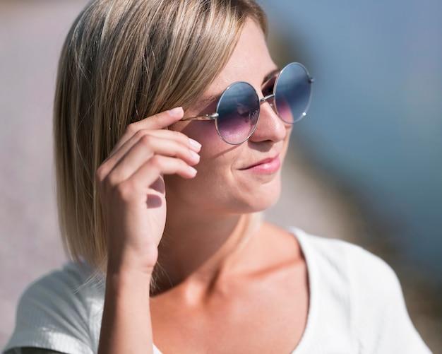 Smileyvrouw die zonnebrilclose-up draagt