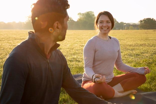 Smileyvrouw en man die buiten op yogamat mediteren