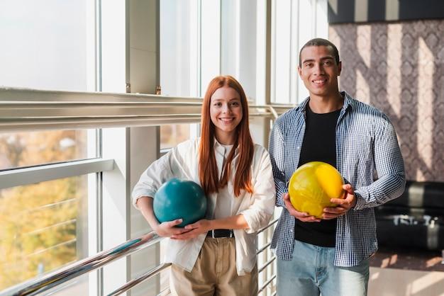 Smileyvrouw en man die kleurrijke kegelenballen houden