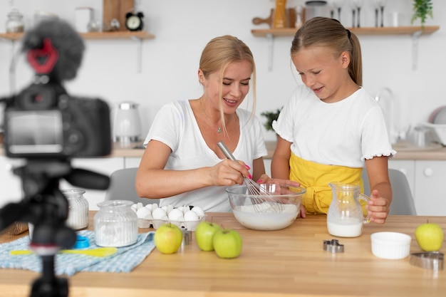 Smileyvrouw en meisje koken